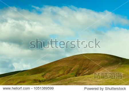 Minimalist landscape of rolling hillside under cloudy skies in north eastern high desert of Oregon near Pendleton.