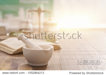 Mortar and pestle with pharmaceutical preparations's book and herbs on a wooden pharmacist table  traditional medicine and pharmacy concept