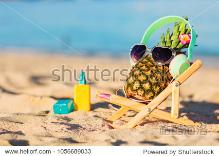 Ripe attractive girl-pineapple in stylish headphones lying on sunbed on the sand against turquoise sea. Listening music  relaxing. Wearing sunglasses. Tropical summer vacation concept. Sunbathing