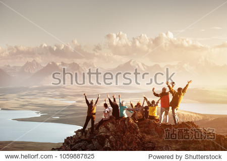 Big group of people having fun in success pose with raised arms on mountain top against sunset lakes and mountains. Travel  adventure or expedition concept