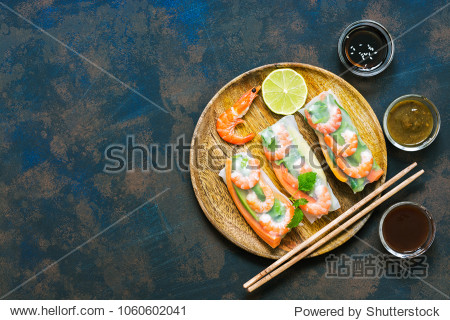 Asian food spring rolls with shrimps on a dark rustic background. Spring rolls in rice paper with a variety of sauces. Top view  space for text