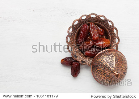 Plate of pitted dates on a white wooden background. Top view