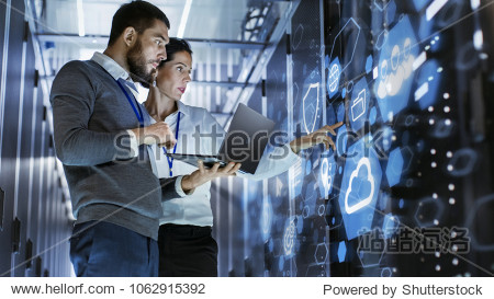 Male IT Specialist Holds Laptop and Discusses Work with Female Server Technician. They're Standing in Data Center  Rack Server Cabinet with Cloud Server Icon and Visualization.