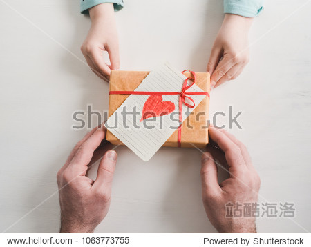 Beautiful box with a gift  a red ribbon  a card with a heart  a loving father's hands and the youngest daughter on a white background. View from above. Preparation for Father's Day