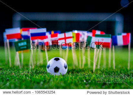 Football ball on green grass and all national flags of FIFA World Cup, Russia 2018.