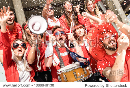 Young football supporter fans cheering with flag and confetti watching soccer match at stadium - Friends people group with red t-shirts having excited fun on sport world championship concept