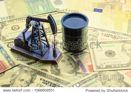 Petroleum  petrodollar and crude oil concept : Pump jack and a black barrel on US USD dollar notes  depicts the money received or earned from sales after investment in the development of oil industry.