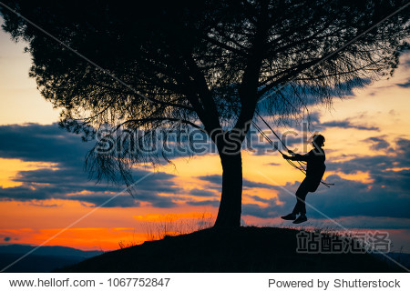 Silhouette of a young woman enjoying freedom at sunset.Tire swinging from a tree outdoors. Holiday concept.