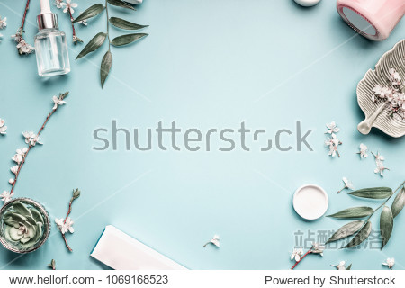 Beauty background with facial cosmetic products  leaves and cherry blossom on pastel blue desktop background. Modern spring skin care layout  top view  flat lay.