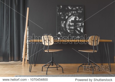 Black and white painting standing against a dark wall  on a wooden dining table in monochromatic room interior