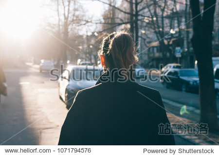 Rear view of young woman wearing black coat walking down the street  sun shine against her. A girl with a ponytail hairstyle goes along the autumn city.