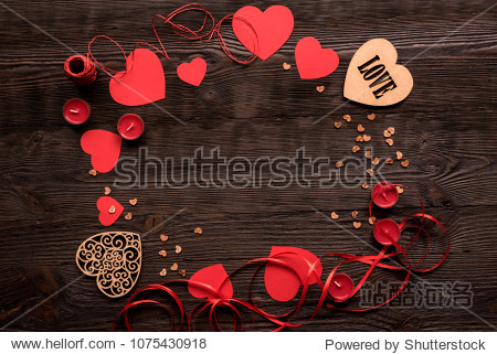 Two wooden hearts with some red hearts and red ribbon on wooden background  place for text in center