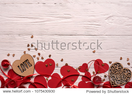 Two wooden hearts with some red hearts and red ribbon on white wooden background  place for text