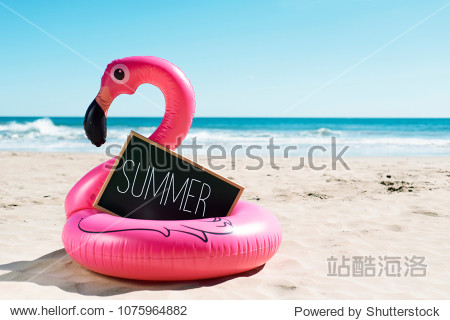 a signboard with the word summer written in it and a swim ring in the shape of a pink flamingo  on the sand of a beach  with the ocean in the background