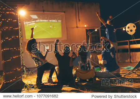 Group of young friends watching a football match on a building rooftop, drinking beer and cheering. Selective focus on the people in the middle