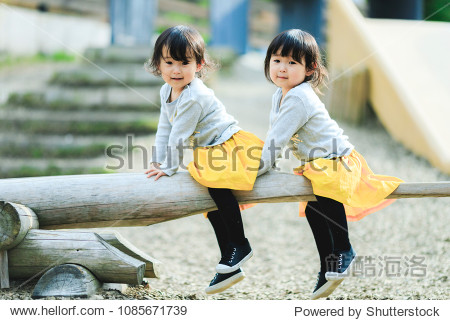 Twins playing in the park's seesaw