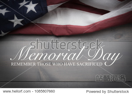The flag of the United Sates of America on a grey plank background with memorial day