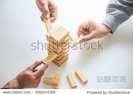 Alternative risk plan and strategy in business  Young intelligent business team playing the wood game  hands of executive cooperation placing wood block on the tower  Collaborative management.