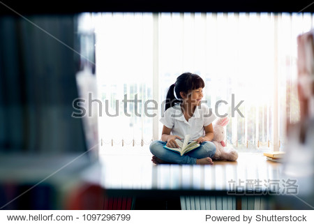 Happy cute little child girl reading a book at library