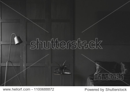 Fern on the table between lamp and bed in monochromatic dark bedroom interior with wooden wall