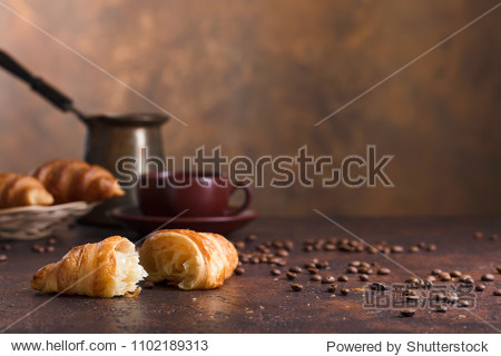 Fresh and tasty croissant  and cup of coffee on old copper background. Free space for your text.