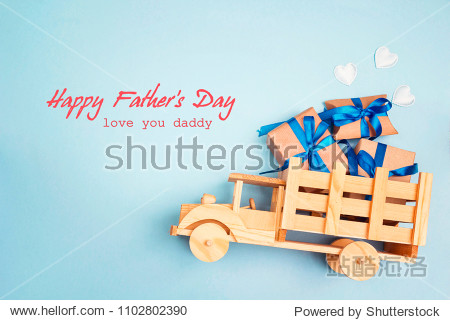 Father's Day greeting message with wooden toy truck with gift box in the back on blue background. Happy fathers day concept.