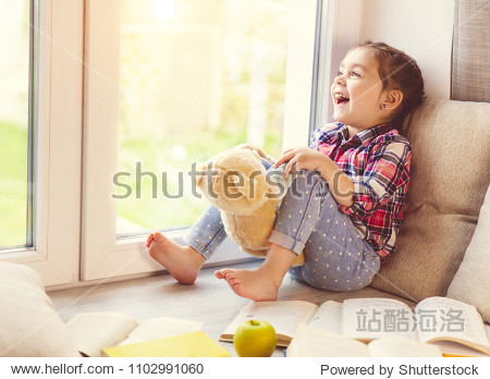 Cute little toddler girl sitting by the window with her teddy bear and laughing.