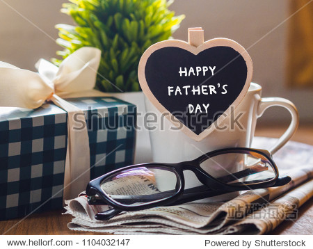 Happy fathers day concept. coffee cup with gift box  heart tag with Happy father's day text and newspaper  glasses on wooden table background.