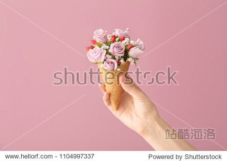 Woman holding waffle cone with beautiful flowers on color background