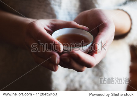 The girl's hands hold the tea bowl.