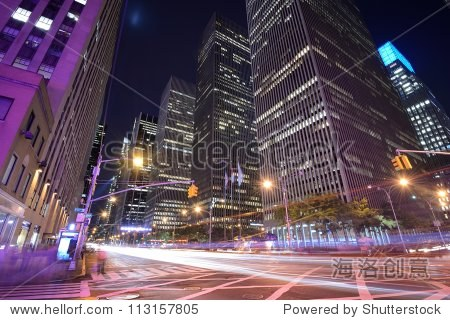 Office buildings at night along 6th Avenue in New York City.