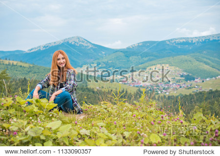 Flowers and romantic woman in the field. Lit evening sun  Beauty Romantic Girl Outdoors. Blowing Long Hair. Autumn. Glow Sun  Sunshine. Toned in warm colors