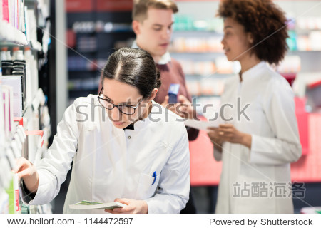 Portrait of a female experienced pharmacist reading the indications from the package of a new pharmaceutical product during work in a contemporary drugstore
