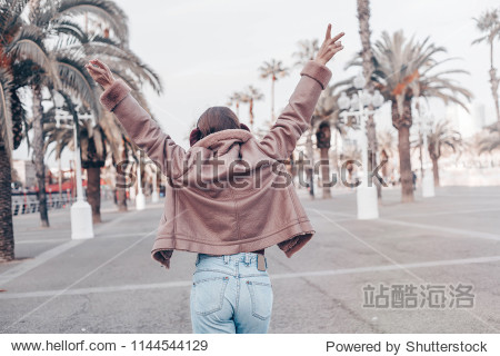 Back view of a young female wanderer out sightseeing in a foreign city during weekend trendy woman traveler in pink jacket and jeans walking on unfamiliar street  spring adventure in Los Angeles