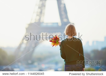 Beautiful young French woman with bunch of colorful autumn leaves near the Eiffel tower in Paris on a fall day
