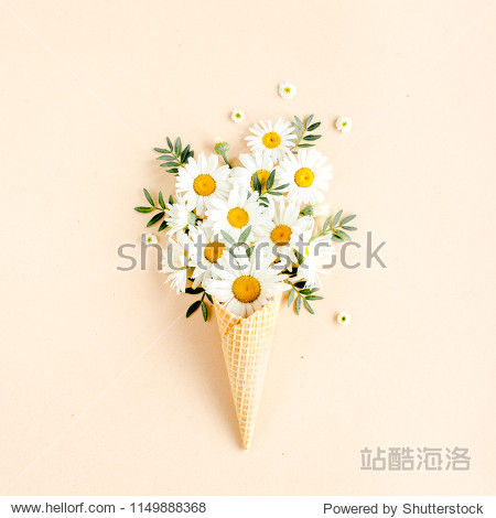 Waffle cone with chamomile flower  leaves on beige background. Flat lay  top view floral background.