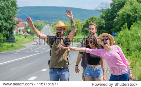 Friends hitchhikers travelling sunny day. Begin great adventure in your life with hitchhiking. Company friends travelers hitchhiking at edge road nature background. Friends looking for transportation.