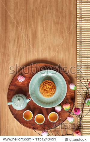 "Traditional Moon cake with chinese  wording ""Kam Lun Egg Yolk "" on plate with cup of tea and flower  mid autumn festival concept with copy space."