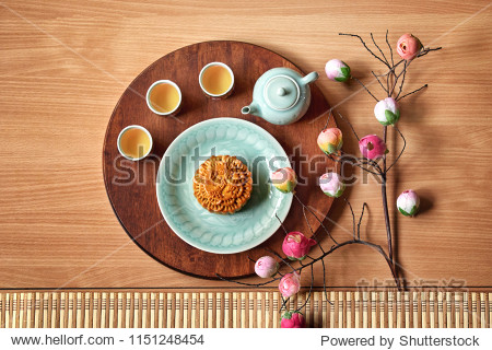 "Traditional Moon cake with chinese  wording ""Kam Lun Egg Yolk "" on plate with cup of tea and flower  mid autumn festival concept"