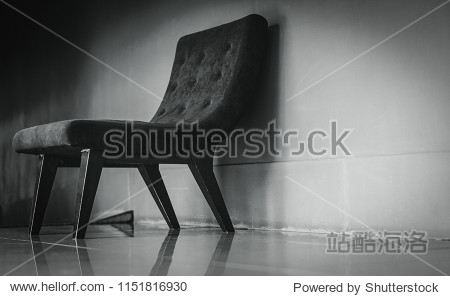 Black classic chair with unique design in empty rest room near concrete wall on dark and dramatic background. Depressed  sad and lonely concept. One empty armchair in living room. Interior furniture.