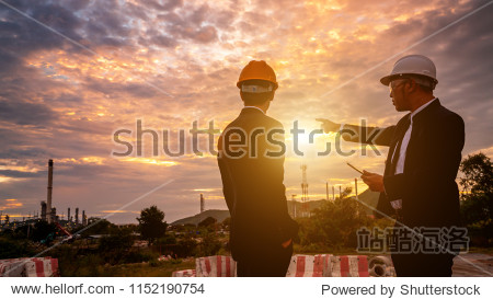 Teams engineer and foreman working at petrochemical oil refinery in sunset