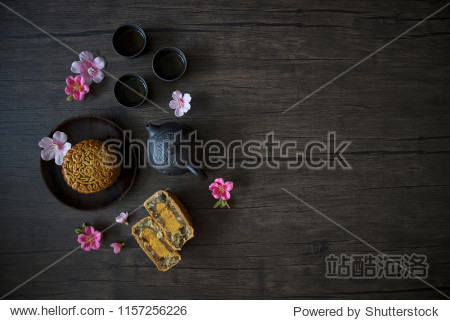 Mooncake flatlay on wooden table. Traditional Baked Mooncake on Dark Background. Mooncakes with Sakura Flowers.
