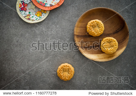 "Traditional baked moon cakes is offered to friends or family during Mid-Autumn Festival. Flatlay table top view dark background with copy space. The Chinese character represent ""lotus paste"""