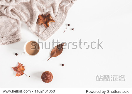 Autumn composition. Cup of coffee  women fashion csweater  autumn leaves on white background. Flat lay  top view  copy space