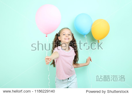 Cute young girl with colored balloons on mint background
