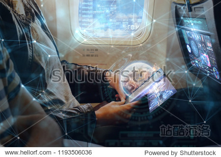 A man on plane uses the phone thanks to the wi-fi present in flight. He uses holography futuristic. Concept of: travel  vacation  technology  future.