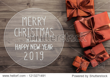 Happy New Year 2019. Merry Christmas text with red gift boxes on wooden background  top view