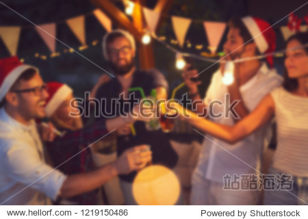Group of young friends having fun at an outoodr poolside New Year's Eve party  making a midnight countdown toast. Blurred people background