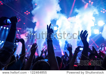 Picture of rock concert  music festival  New Year eve celebration  party in nightclub  dance floor  disco club  many people standing with raised hands up and clapping  happiness and night life concept