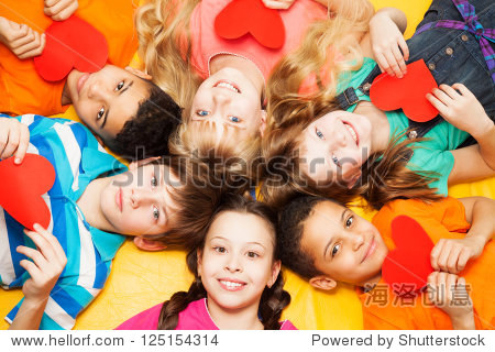 Kids laying in circle with hearts in their hands smiling  boys and girls with diversity